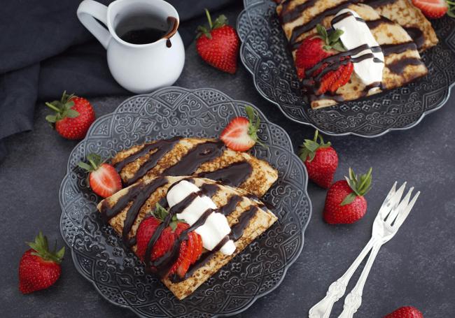 Glutenfria pannkakor med fiberhusk serverade med grädde, jordgubbar och smält choklad